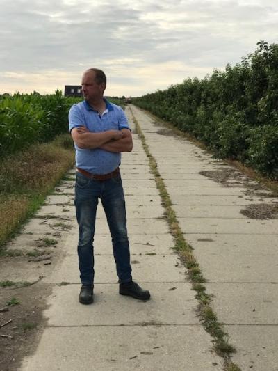 Fruitteler Rogier van Damme te midden van het fruit (rechts) en de maïs (links) die op de eigenlijke fruitteeltgrond is ingezaaid. Hij ziet de toekomst met een bedenkelijke blik tegemoet
